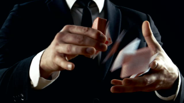Close-up of a Suited Magician's Hands Performing Card Trick. Throwing and Catching Cards in the Air. Background is Black. Sleight of Hand. Slow Motion. Close-up of a Suited Magician's Hands Performing Card Trick. Throwing and Catching Cards in the Air. Background is Black. Sleight of Hand. Slow Motion. Shot on RED EPIC-W 8K Helium Cinema Camera. playing card stock videos & royalty-free footage