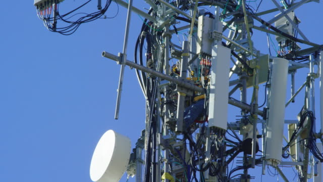 Close-Up of a Technician Assembling a Cell Phone Tower on a Clear, Sunny Day
