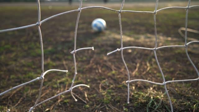 stockvideo's en b-roll-footage met close-up van een gescheurd voetbalnet. voetbal bal door het net. oud poortvoetbalgebied. - sportcompetitie