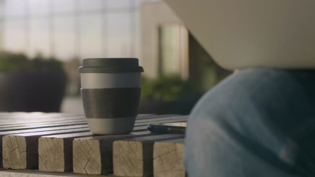 Close-up of a Travel Mug next to a man working on the go