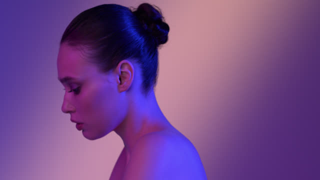 Close-up of a twist of a shiny face of a girl with blue make-up in colored light. video