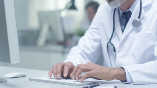 Nahaufnahme von weißen Haaren Senior Arzt und seinem Assistenten arbeiten bei Desktop-Computern. Arbeiten in hell beleuchteten Büro. – Video