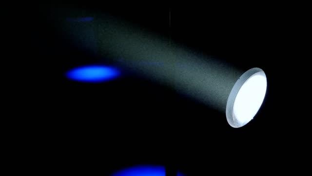 vídeos y material grabado en eventos de stock de primer plano de un foco blanco que brilla en el escenario en la oscuridad. - aleación