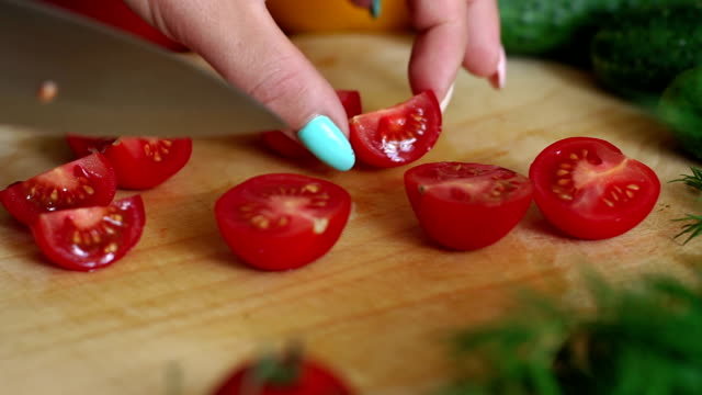Close-up of a woman chef cuts a ripe tomato on a wooden chopping Board.