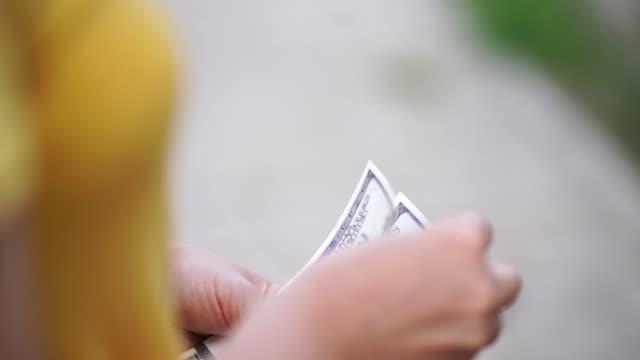 nahaufnahme einer frau, die geld zählt. dollar in den händen von - weibliche angestellte stock-videos und b-roll-filmmaterial