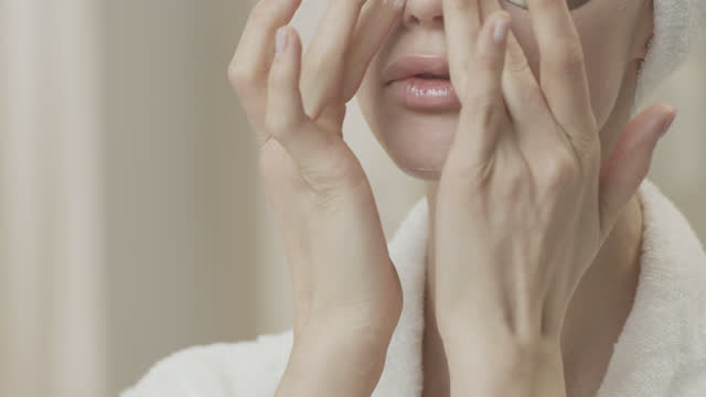 Close-up of a woman head in a white towel, who applies moisturizer to her face. video
