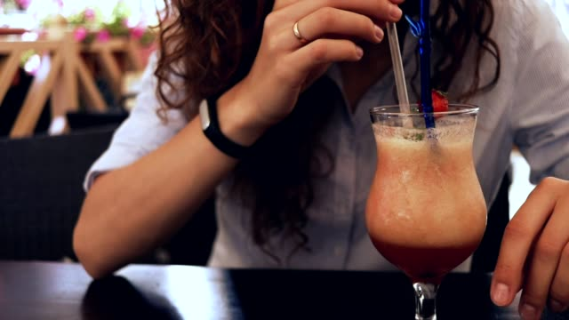 Close-up of a woman in a cafe drinking a cocktail with a straw, slow motion video