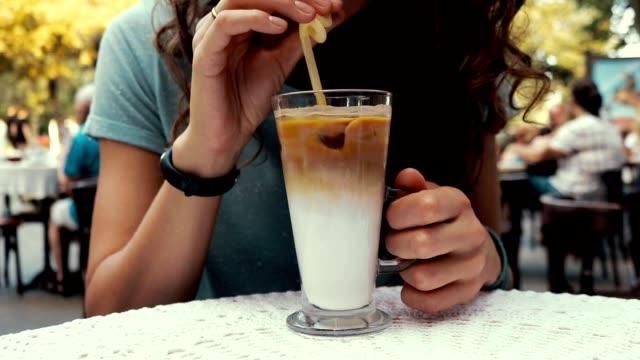 närbild av en kvinna i ett kafé som dricker kaffe med mjölk och is utomhus - sugrör bildbanksvideor och videomaterial från bakom kulisserna
