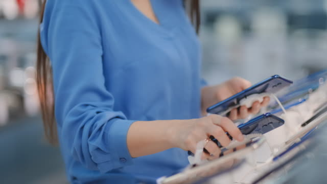 Close-up of a woman in an electronics store holding in her hands two new smartphone and chooses the best one standing near the showcase with gadgets Close-up of a woman in an electronics store holding in her hands two new smartphone and chooses the best one standing near the window with gadgets. electrical equipment stock videos & royalty-free footage