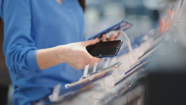 Close-up of a woman in an electronics store holding in her hands two new smartphone and chooses the best one standing near the showcase with gadgets