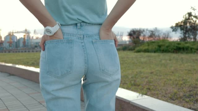 close-up of a woman in jeans and a t-shirt waiting for a meeting. view from the back, slow motion. - jeans video stock e b–roll