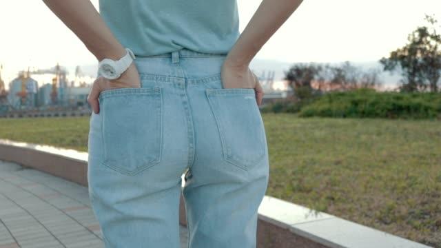 närbild av en kvinna i jeans och en t-shirt som väntar på ett möte. visa från baksidan, slowmotion. - byxor bildbanksvideor och videomaterial från bakom kulisserna
