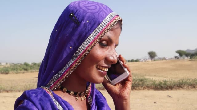 closeup of a woman in traditional clothes and jewelry talking on her phone - country fashion stock videos & royalty-free footage