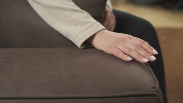 A close-up of a woman sitting on sofa and touching its upholstery. Isolated, on blurred background
