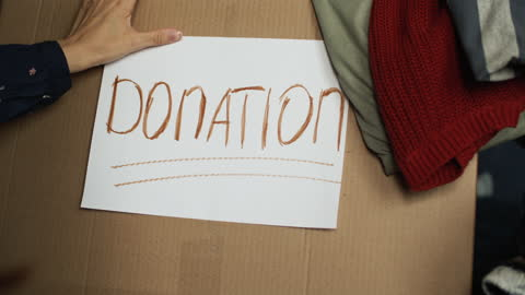 """Close-up of a woman sticking """"Donation"""" to a Donations box Woman preparing clothes to donate. BMPCC 4k. giving tuesday stock videos & royalty-free footage"""