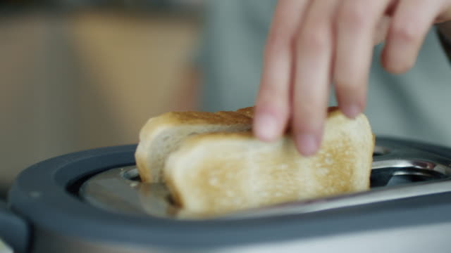 Close-up of a Woman Taking Toasts out of a Toaster. video