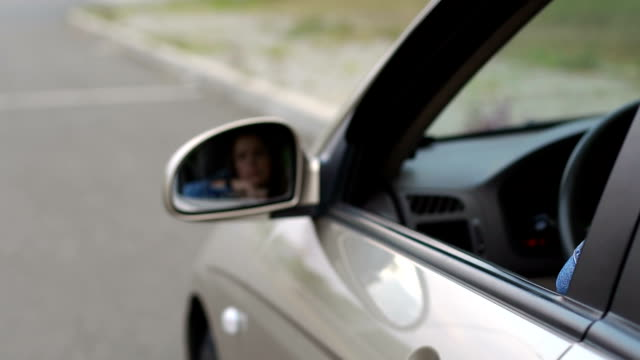 Close-up of a woman throwing garbage out of a car window.