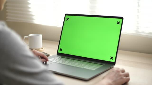 vídeos de stock, filmes e b-roll de close-up de uma mulher usa laptop com tela verde mock-up - panning