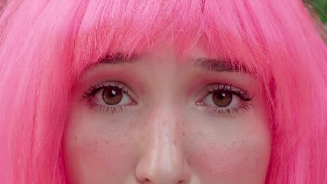 stockvideo's en b-roll-footage met close-up van een vrouw met roze haar dat de camera bekijkt. - roze haar