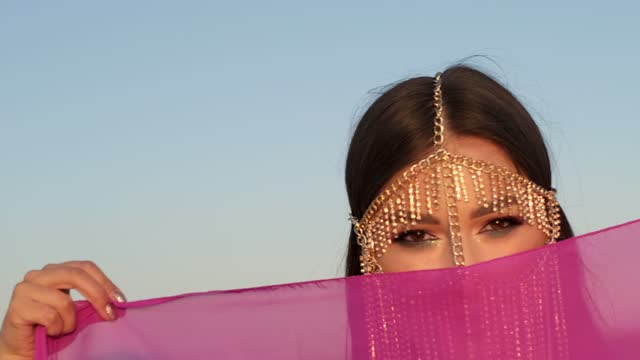 Closeup of a woman's face with jewelry on her head in oriental style. Beautiful woman looks into the camera. Cloudy sky. Sunset.