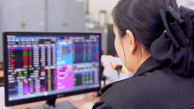 Close-up of a woman's hand investing in the stock market online from computer, Stock exchange and trading online,