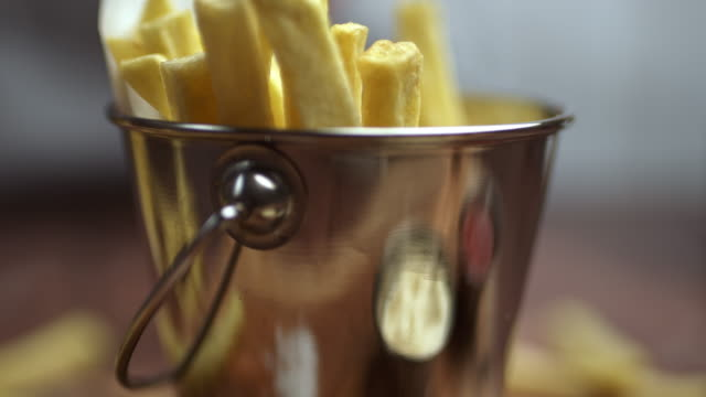 A close-up of a woman's hand taking a piece of waged fries French Fries and braking in two. Serving chips from a Basket.