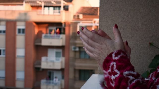 A close-up of a woman's hands as she is clapping from her balcony