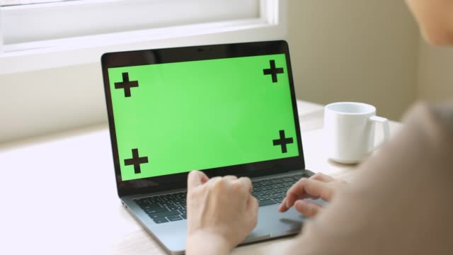 stockvideo's en b-roll-footage met close-up van een vrouw handen met behulp op groen scherm op een laptop thuis - aziatische etniciteit