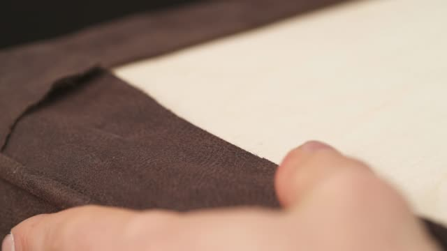 A close-up of a worker fixing fabric with industrial stapling machine in a workshop of factory. Sofa making concept