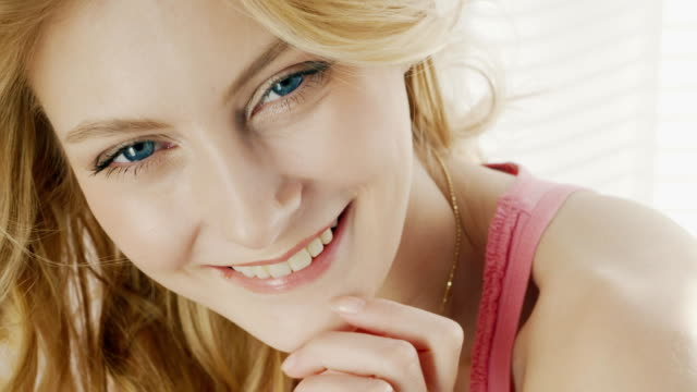 Close-up of a young attractive woman. Natural lighting, looking at the camera and smiling video