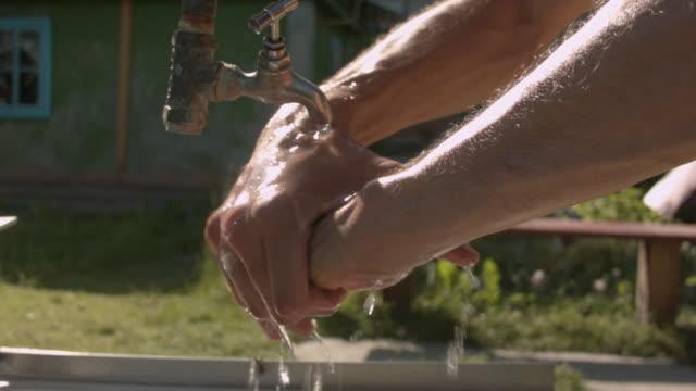 庭の夏に洗面台で手を洗う若い白人男性のクローズアップ。 - 体 洗う点の映像素材/bロール