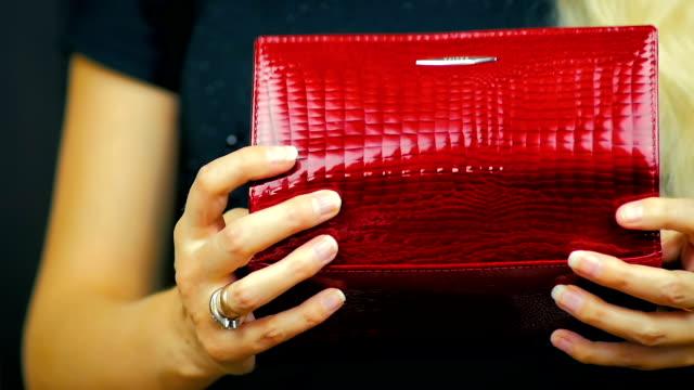 關閉一個年輕的女孩關閉一個紅色的錢包, 其中有現金和信用卡在慢動作 - 銀包 個影片檔及 b 捲影像