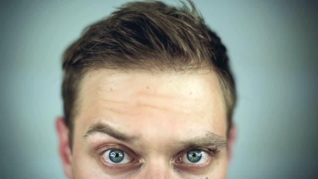 vídeos de stock e filmes b-roll de close-up de um jovem olhos verde grande homem levantar sobrancelha sobre fundo branco - sobrancelha