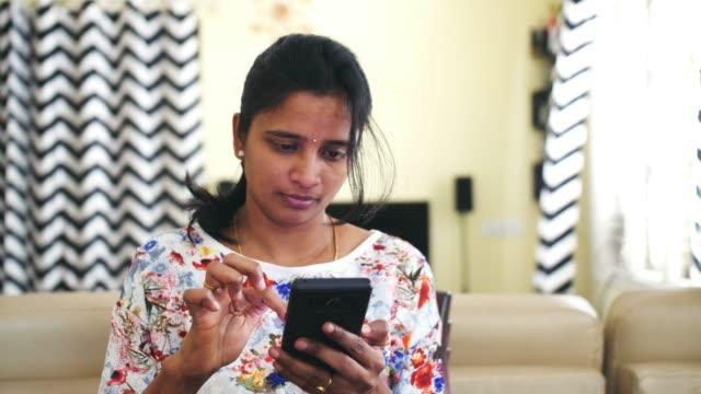 vídeos de stock, filmes e b-roll de close-up de uma jovem indiana operando um telefone celular - camiseta preta