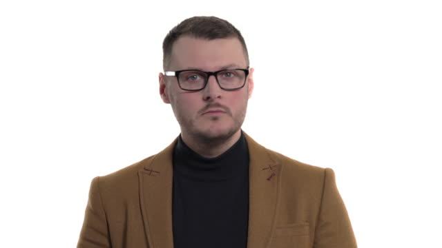 stockvideo's en b-roll-footage met close-up van een jonge mens kleding zijn mond dicht met palm. lichaamstaalconcept - men blazer
