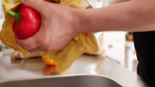 Close-up of a young man washing peppers in the kitchen sink and carrying them to the table