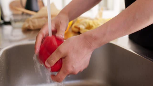 vidéos et rushes de gros plan d'un jeune homme se laver les poivrons dans l'évier de cuisine - cuisine non professionnelle