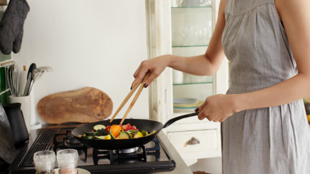 Close-up of a young woman cooking stir fry in wok