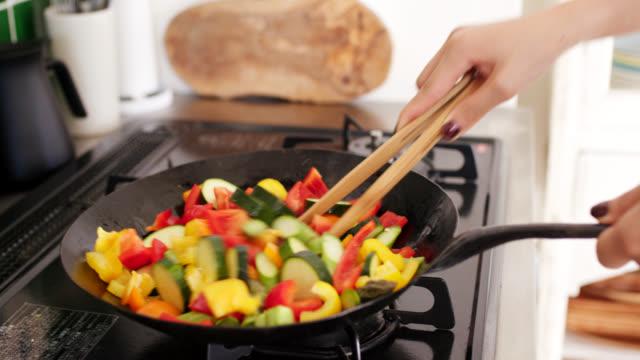 vidéos et rushes de gros plan d'une jeune femme faisant cuire des légumes dans un wok - cuisine non professionnelle