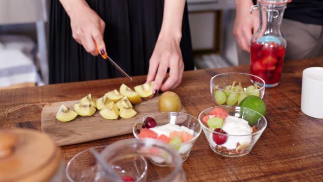 vidéos et rushes de gros plan d'une jeune femme coupant un fruit de kiwi - en cas