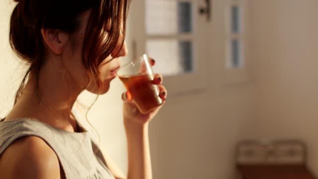 nahaufnahme einer jungen frau, die zu hause tee trinkt - grüner tee stock-videos und b-roll-filmmaterial