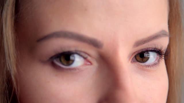 若い女性の目のクローズ アップは、彼女のカメラに視線は、彼女の笑顔、彼女の目を明るくします。 - まつげ点の映像素材/bロール