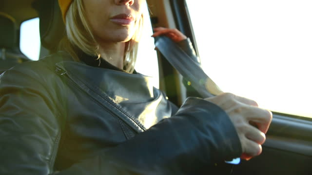 Close-up of action girl fastens a seat belt in a car before dropping off