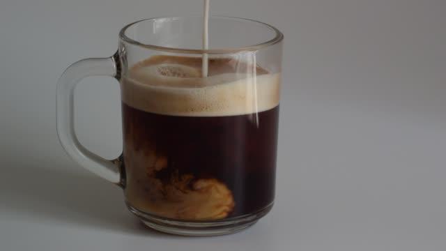 nahaufnahme von einem glaskrug mit frischen duftenden schwarzen kaffee mit schaum crema milch hinzufügen - cappuccino stock-videos und b-roll-filmmaterial
