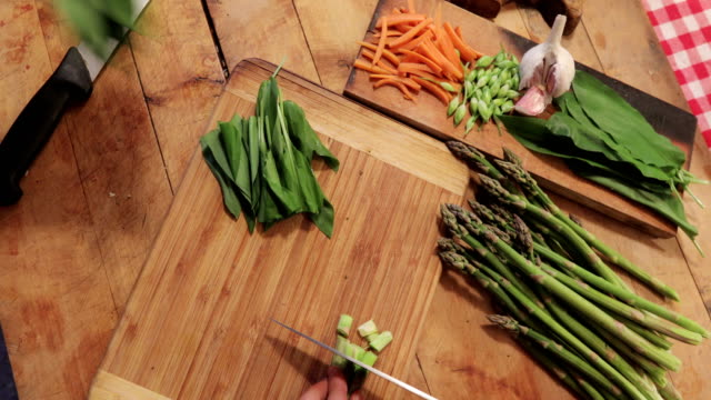 Close-up of Adult Man and Woman Chopping Asparagus and Ramson