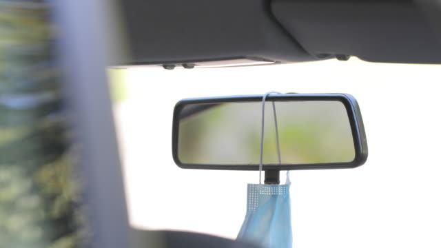 stockvideo's en b-roll-footage met close-up van volwassen mens die beschermend gezichtsmasker op spiegel van het gezicht van de achterzijde in auto hangt - mirror mask