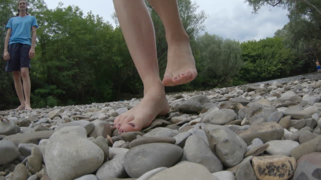 Close-up of Adult Woman Walking Barefoot on Pebbles on Riverbank