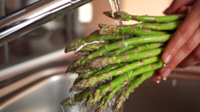 Close-up of Adult Woman Washing Asparagus