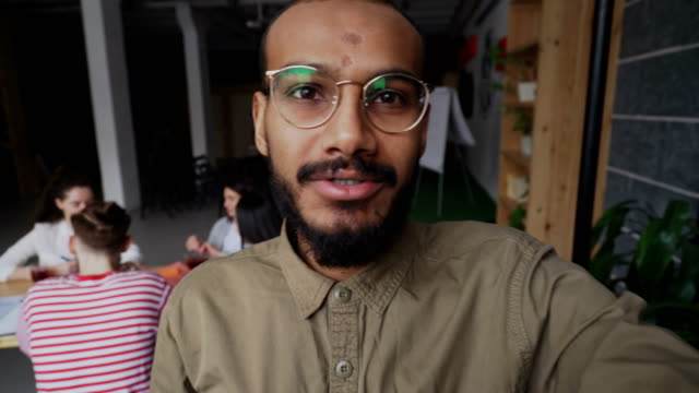 Close-up of african american hipster man in glasses holding smartphone and have onlive video call while his colleagues working in modern office video