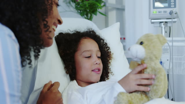 close-up of african american mother and son playing with teddy bear in the ward at hospital 4k - jeden rodzic filmów i materiałów b-roll